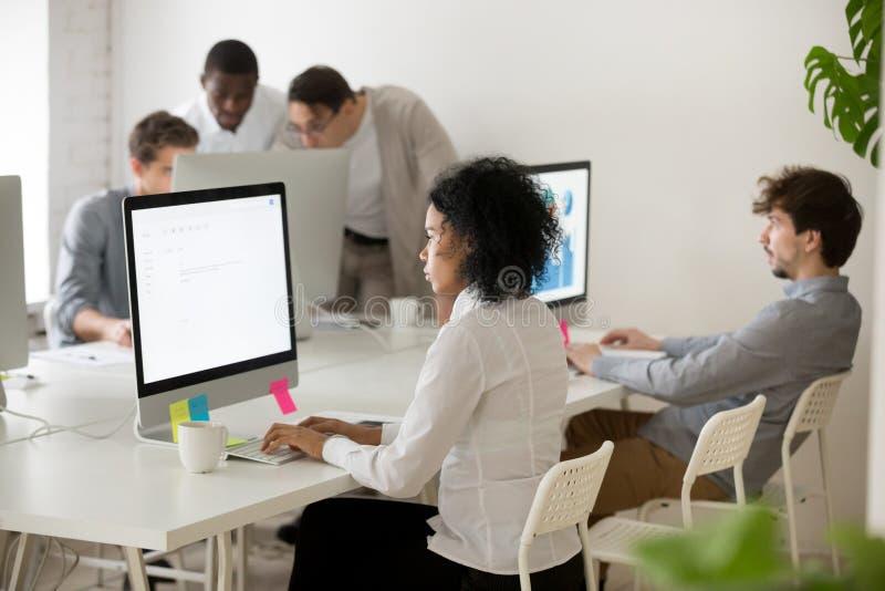 Afroamerikanerfrauenmanager konzentrierte sich auf Computerarbeit in multi stockfotografie