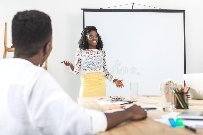 Afroamerikanergeschäftsfrau, die neues Geschäftskonzept vorstellt lizenzfreies stockbild