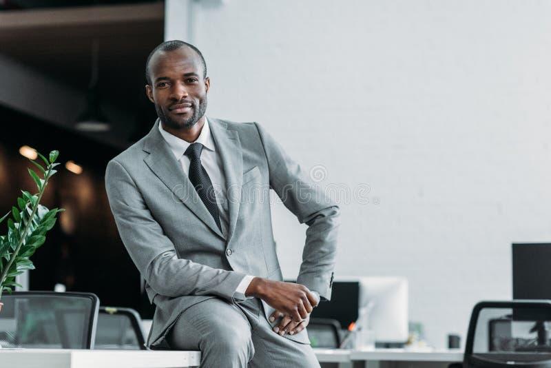 Afroamerikanergeschäftsmann, der auf Tabelle sitzt stockbilder