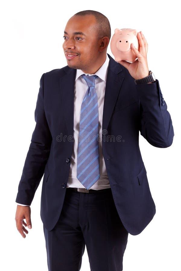 AfroamerikanerGeschäftsmann, der ein Sparschwein - afrikanisches peo hält stockbilder