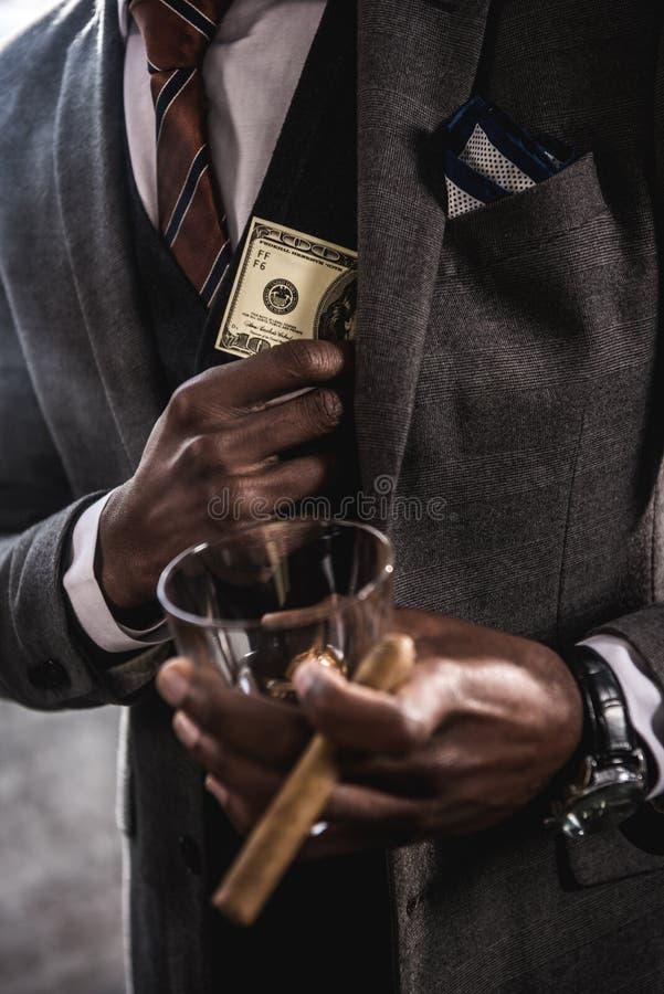 Afroamerikanergeschäftsmann, der Glas des Alkoholgetränkes und -zigarre beim Verstecken der Dollarbanknote hält stockfotos