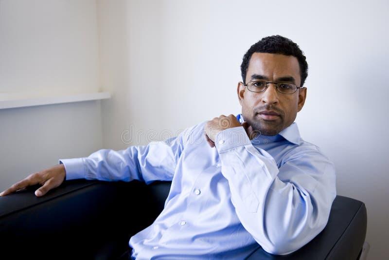 Afroamerikanergeschäftsmann, der im Lehnsessel sitzt stockfotografie