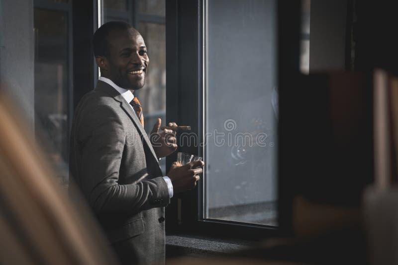 Afroamerikanergeschäftsmann in der Klage mit Glas der rauchenden Zigarre des Whiskys lizenzfreie stockfotos