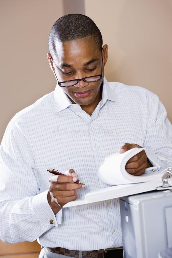 Afroamerikanergeschäftsmann-Lesedokument lizenzfreie stockfotografie