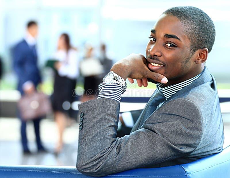 AfroamerikanerGeschäftsmann mit den Führungskräften, die im Hintergrund arbeiten lizenzfreie stockfotografie