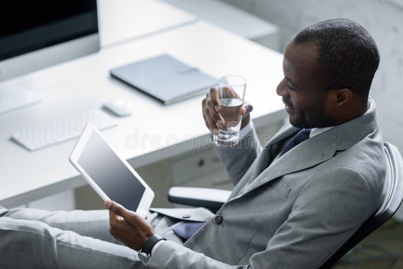 Afroamerikanergeschäftsmann mit Glas Wasser unter Verwendung der Tablette am Arbeitsplatz stockfoto