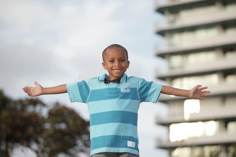 Afroamerikanerjunge mit den Armen ausgestreckt stockfotos