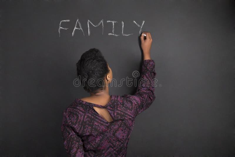 Afroamerikanerlehrerin-Schreibensfamilie auf Kreideschwarz-Bretthintergrund stockbilder