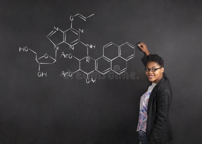 Afroamerikanerlehrerin-Schreibenswissenschaft auf Kreideschwarz-Bretthintergrund stockfotografie