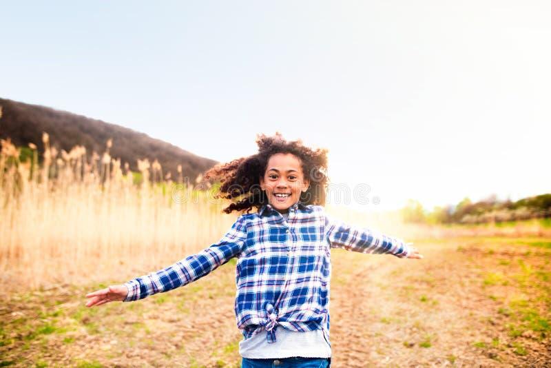 Afroamerikanermädchen in überprüftem Hemd draußen auf dem Gebiet lizenzfreie stockfotos