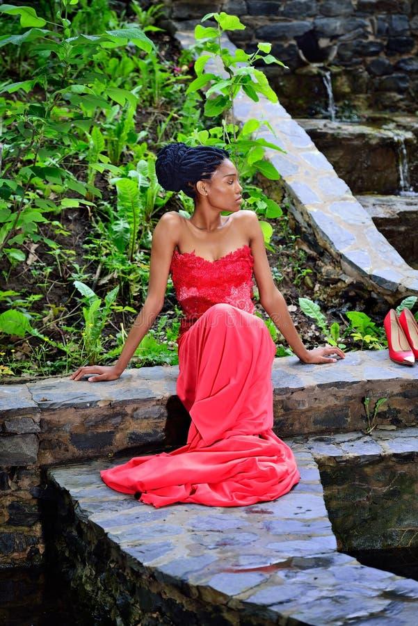 Afroamerikanermädchen, das auf den Steinen im Park auf einem Hintergrund von Grünpflanzen sitzt und zur Seite schaut stockbild