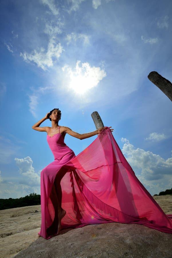 Afroamerikanermädchen in der rosa Kleideraufstellung und Spiele mit ihr Kleid auf einen Hügel gegen den Himmel und die Sonne stockbild