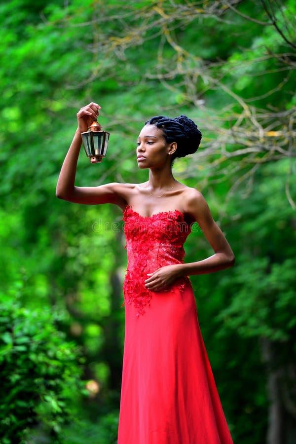 Afroamerikanermädchen in einem roten Kleid, mit Dreadlocks, mit einer Lampe und einer Kerze in seiner Hand, steht im Park im Somm lizenzfreies stockfoto