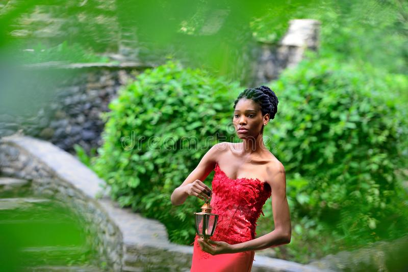Afroamerikanermädchen in einem roten Kleid, mit Dreadlocks, mit einer Lampe und einer Kerze in seiner Hand, werfend im Park auf stockfoto