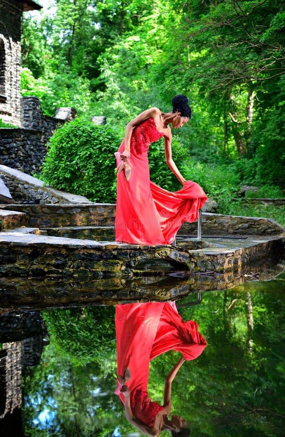 Afroamerikanermädchen in einem roten Kleid mit roten Schuhen ist in der Hand im Sommer auf dem Wasser auf den Steinen im Park wer lizenzfreie stockfotos