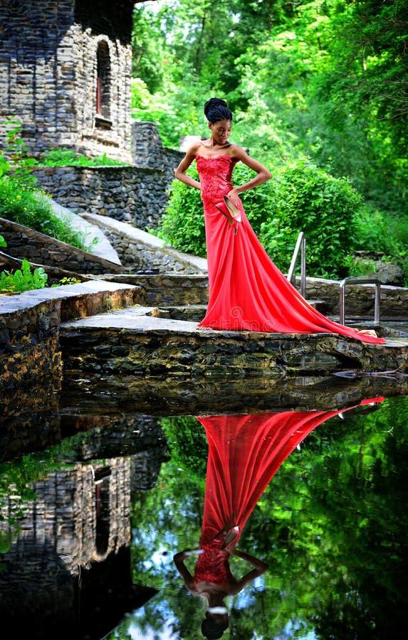 Afroamerikanermädchen in einem roten Kleid mit roten Schuhen ist in der Hand im Sommer auf dem Wasser auf den Steinen im Park wer stockbilder