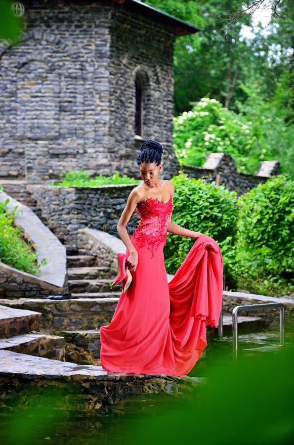Afroamerikanermädchen im roten Kleid, das im Park im vollen Wachstum aufwirft lizenzfreie stockfotografie