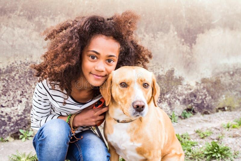 Afroamerikanermädchen mit ihrem Hund gegen Betonmauer lizenzfreie stockfotos
