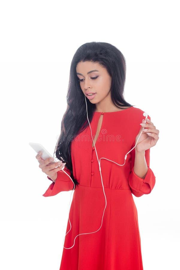 Afroamerikanermädchen in rotes Kleiderhörender Musik in den Kopfhörern mit dem Smartphone lokalisiert lizenzfreies stockbild