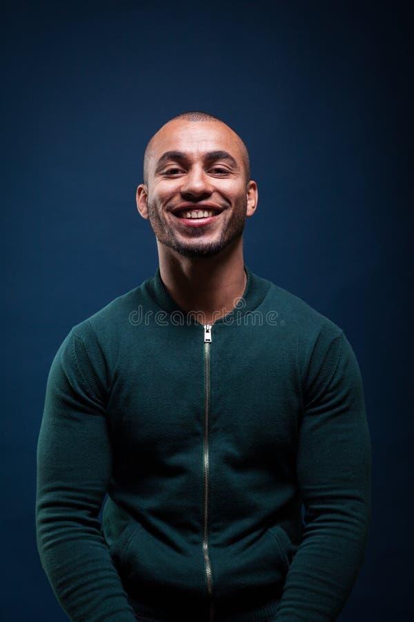 Afroamerikanermann, der auf dunkelblauem Hintergrund lächelt lizenzfreie stockbilder