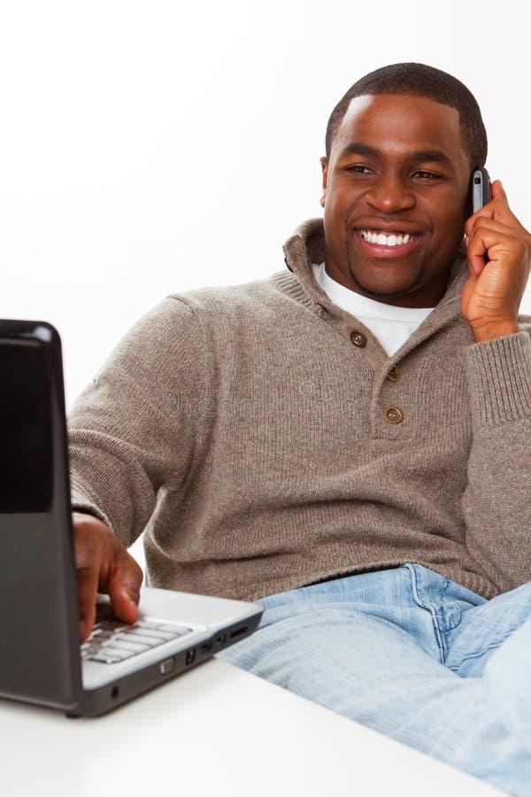 Afroamerikanermann, der an dem Computer arbeitet stockbild