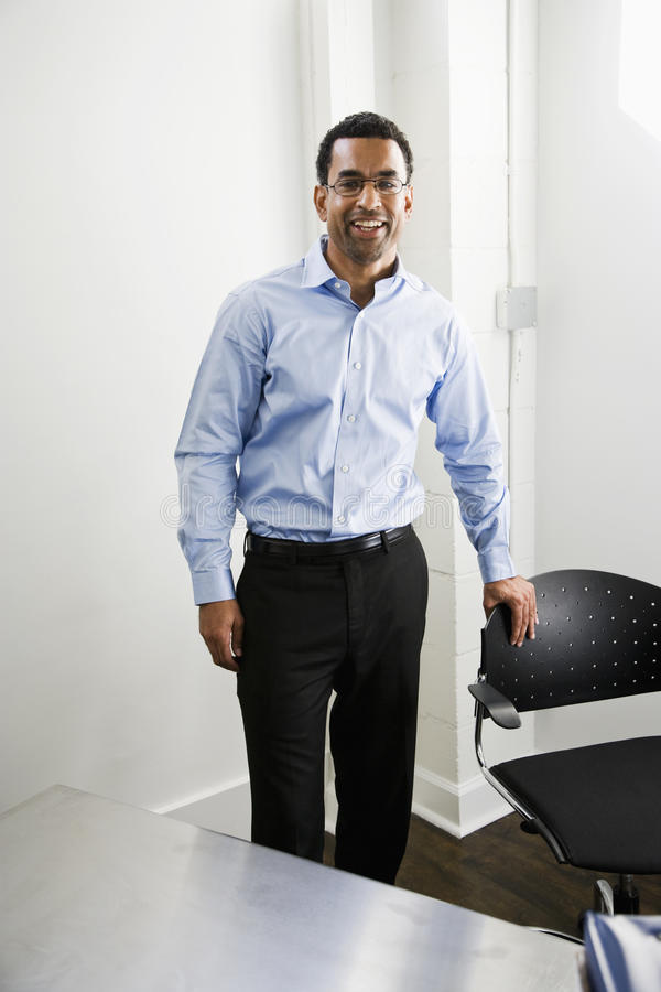 Afroamerikanermann, der im Büro steht lizenzfreie stockbilder