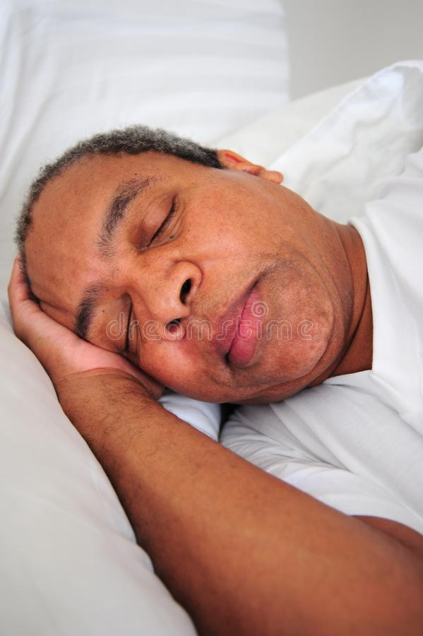 Afroamerikanermann, der im Bett schläft lizenzfreie stockbilder