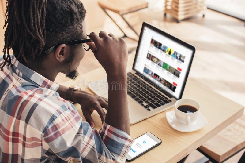 Afroamerikanermann, der Laptop mit Youtube-Website und -Smartphone verwendet lizenzfreies stockbild