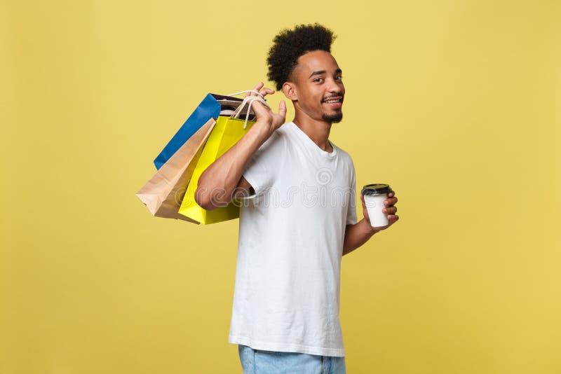 Afroamerikanermann mit den bunten Papiertüten lokalisiert auf gelbem Hintergrund lizenzfreies stockbild