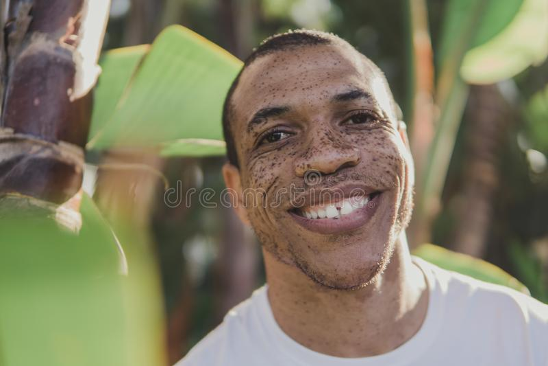 Afroamerikanermann mit Sommersprossen draußen lächelnd stockfoto