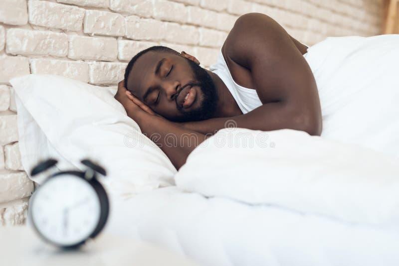 Afroamerikanermann schläft im Bett lizenzfreies stockfoto
