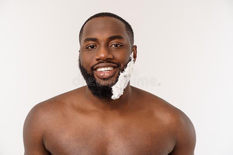 Afroamerikanermann schmiert Rasierschaum auf Gesicht durch Rasierpinsel M?nnliche Hygiene Getrennt auf wei?em Hintergrund studio lizenzfreie stockfotos