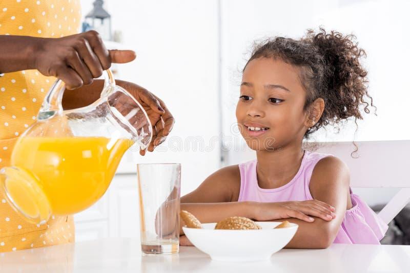 Afroamerikanermutter, die Orangensaft für Tochter gießt stockbilder