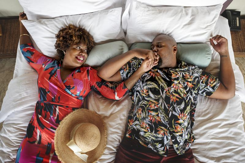 Afroamerikanerpaare, die auf einem Bett sich entspannen stockbilder