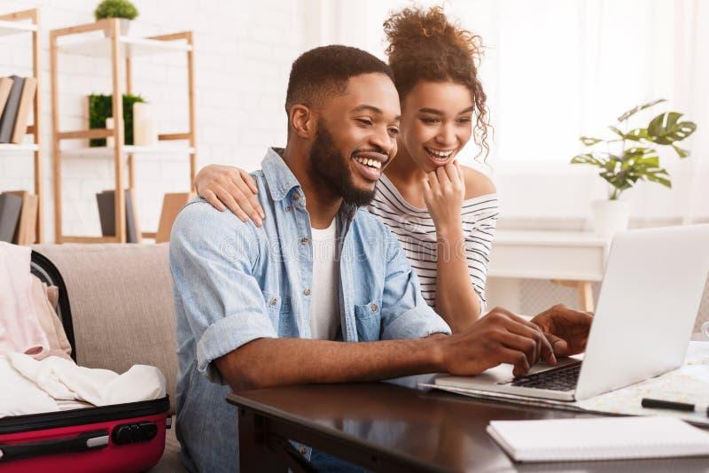 Afroamerikanerpaare, die Ausflug online auf Laptop suchen stockfotos