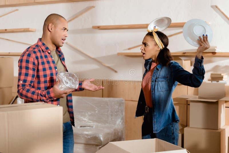 Afroamerikanerpaare, die in der neuen Wohnung auspacken und streiten stockfoto