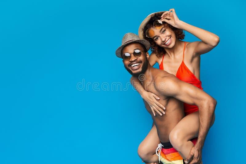 Afroamerikanerpaare, die, Mann huckepack tr?gt seine Freundin t?uschen stockfoto