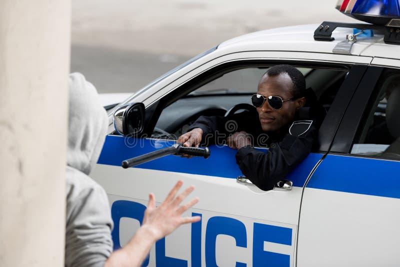 Afroamerikanerpolizist, der mit Kapuze Mann mit Polizeischläger beim Schauen stoppt lizenzfreie stockbilder