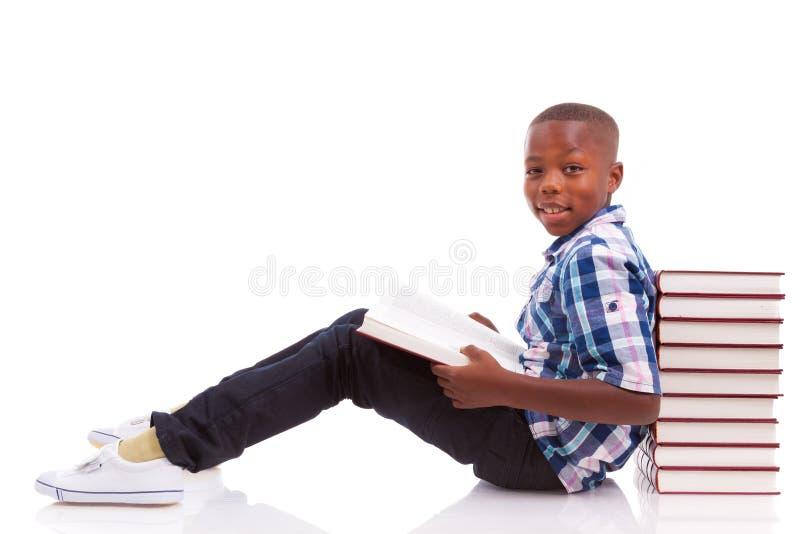 Afroamerikanerschuljunge, der ein Buch - schwarze Menschen liest stockfoto