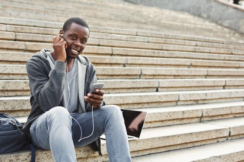Afroamerikanerstudent, der auf Treppe sitzt und draußen Musik hört lizenzfreie stockfotos
