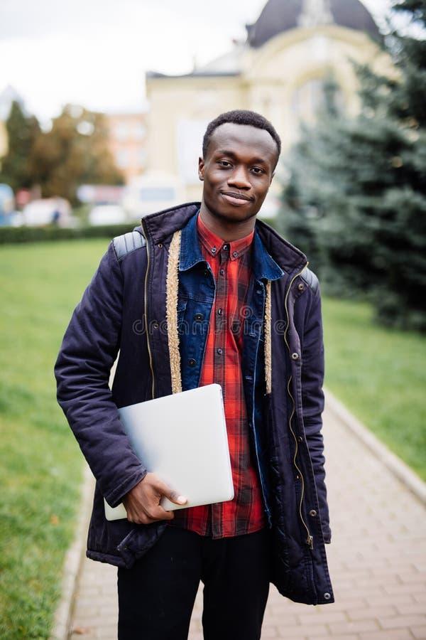 AfroamerikanerStudent mit der Laptop-Computer, denkend stockfoto