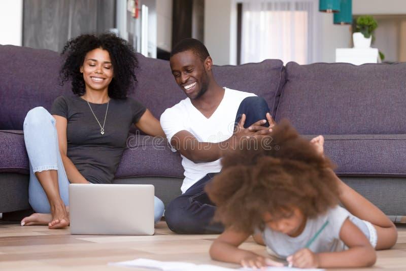 Afroamerikanerverheiratetes paar, das Laptop während Tochterspielen verwendet stockfotos