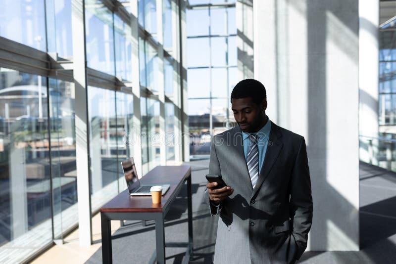 Afroamerikanisch vom Geschäftsmann, der Handy im Büro verwendet stockfoto