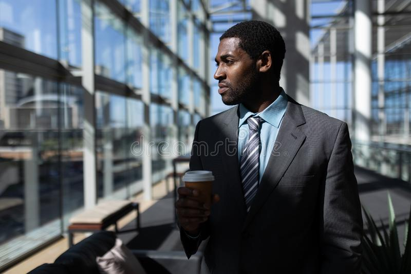 Afroamerikanisch vom Geschäftsmann mit der Kaffeetasse, die weg im Büro schaut lizenzfreies stockbild