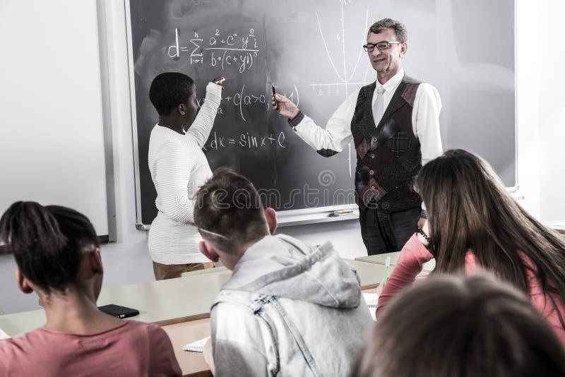 afroamerykański uczeń odpowiada blisko blackboard przy matematyki lekcją obraz stock