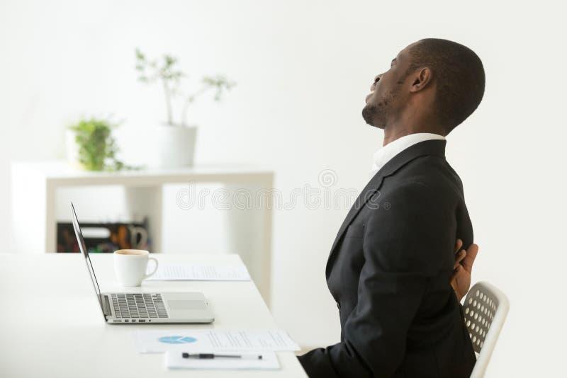 Afroamerykański biznesmen czuje nagłego backache obsiadanie dalej obraz stock