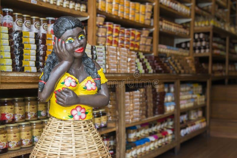 Afrobrazililian在一个食物店的妇女时装模特与地方产品在欧鲁普雷图,米纳斯吉拉斯州,巴西 免版税库存照片