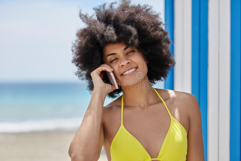Afroe-amerikanisch Frau im gelben Bikini sprechend auf Mobile stockfotografie