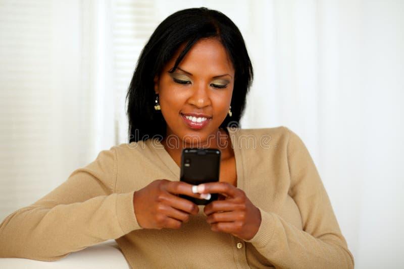 Afroe-amerikanisch junge Frau, die eine Meldung sendet stockfotografie