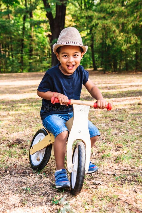 Afroe-amerikanisch oder lateinische Jungenfahrten auf hölzernes Fahrrad im Park lizenzfreie stockfotografie